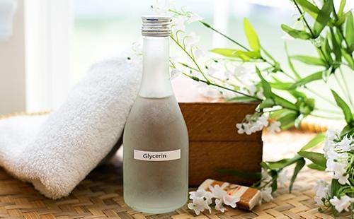 Белые цветы, мягкое полотенце и бутылочка глицерина